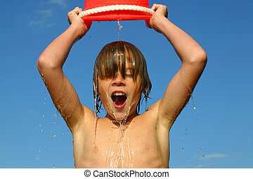 Boy dumping a bucket of water on his head against a blue sky