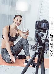 Happy joyful woman holding a glass of water