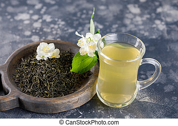 Refreshing drink in a glass cup. Green tea with jasmine.