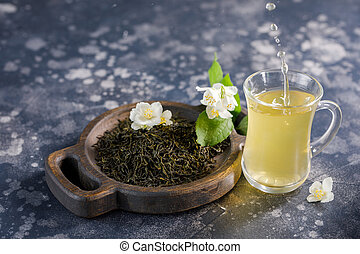 Refreshing drink in a glass cup with splash. Green tea with jasmine.