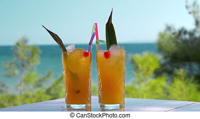 Refreshing fruit drinks with ice cubes falling into glasses
