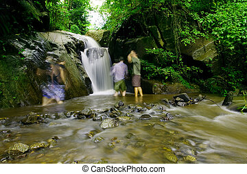 Hikers refresh themselves in a waterfall - time exposure
