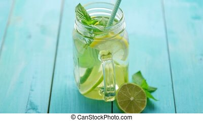 Refreshing lemonade on blue table - From above drinking jar...
