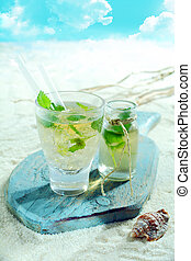 Refreshing mojito cocktail served at the seaside on a tropical beach on an old wooden board