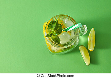 Refreshing natural non-alcoholic cocktail in glass jar with ice cubes, slices of lime and lemon, sprig of mint with plastic straw on a green background. Top view with copy space.