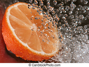 Water drops falling onto an orange - focus is on the water drops