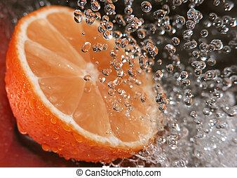 Refreshing orange - Water drops falling onto an orange -...