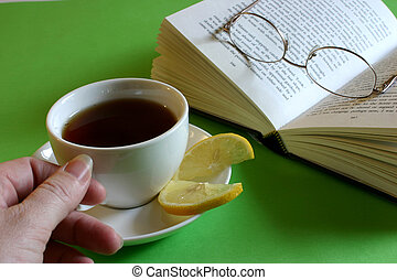 Hand reaching for cup of tea with lemon and book with glasses