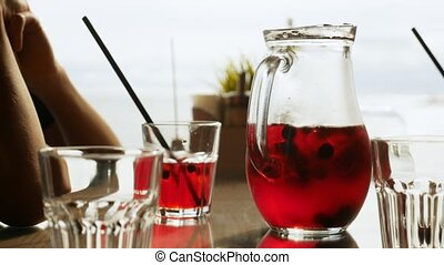 Refreshing red lemonade with berries in a jug on a table in...