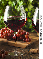 Refreshing Red Wine In a Glass with Grapes