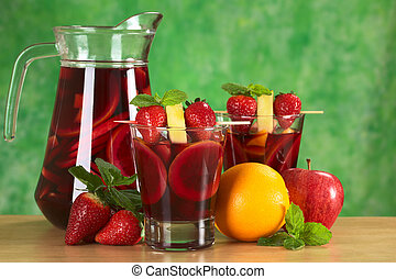 Refreshing red wine punch called sangria mixed with orange, apple and mango, garnished with strawberries and pineapple on skewer with a jug of sangria in the back and fruits around (Selective Focus, Focus on the fruits on the skewer on the first drink)