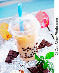 Refreshing sherbet drink with bits of chocolate served in a domed cup with a straw on a hot day