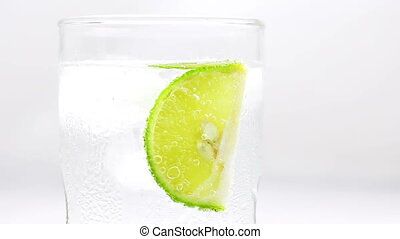 Refreshing soda tonic fizzy water with lime slice in a...