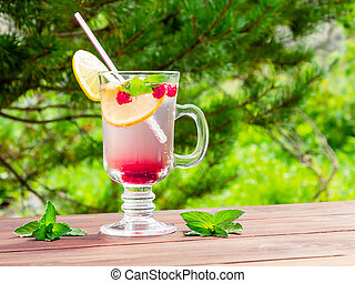 Refreshing summer cocktail with lemon, raspberry and mint a wooden table