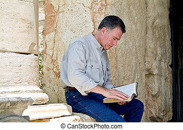 Refreshing the Soul - A man sitting on a stone wall reading...