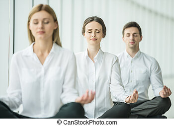 Coworkers meditating at office, taking break with their eyes closed.