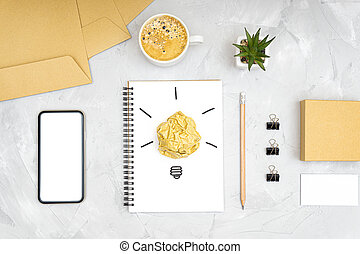 Refreshment break idea and productivity boost concept. Flat lay of an office workplace with a smartphone, coffee cup, light bulb symbol made of a crumpled paper ball and a sketch on a spiral notebook.