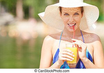 Refreshment - Woman in bikini drinking orange juice