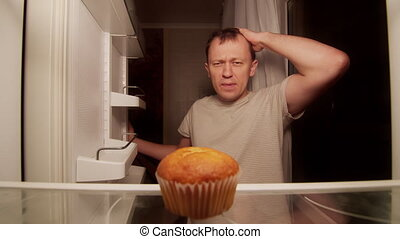 Refrigerator of a lonely man, one spoiled cupcake on the shelf