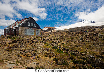 Cottages for tourists (refugio) on mountainside near volcano Tronador and glaciers. Andes, Argentina