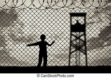 Child refugee, near the fence of barbed wire
