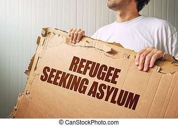 Refugee seeking asylum in foreign country, male immigrant with cardboard banner