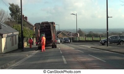 Refuse collectors and truck in action