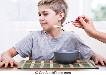 Picky eater boy refusing to eat disgusting food