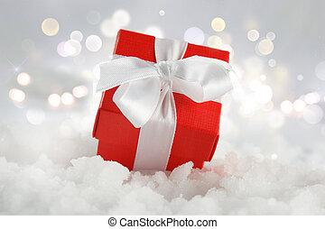 regalo de navidad, anidado, en, nieve, contra, un, bokeh, luces, plano de fondo