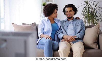 regardant télé, couple, maison, sourire heureux