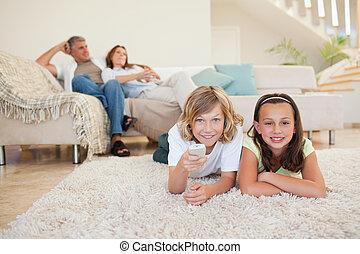 regardant télé, frères soeurs, moquette