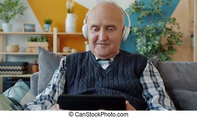 regarder, écouteurs, maison, homme, tablette, porter, vieux, écran, beau
