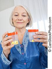 regarder, femme aînée, bouteilles, tablette
