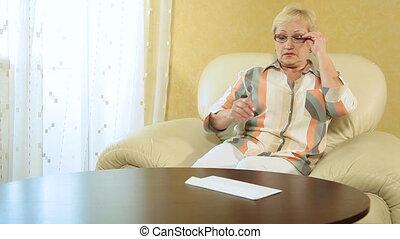 regarder, femme aînée, sur, papiers
