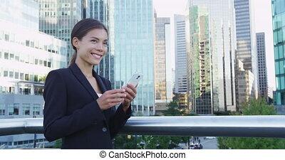regarder, femme affaires, bâtiments, sourire, contre, mobile, quoique, téléphone, loin, tenue