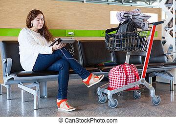 regarder, femme, tablette, bagage, salon, pc, aéroport, hand-cart