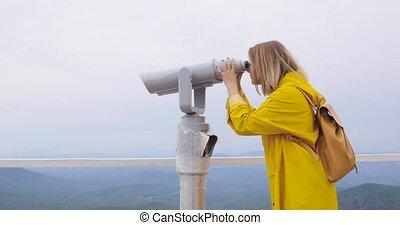 regarder, femme, touriste, imperméable, jaune, jumelles, par, montagnes