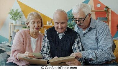 regarder, groupe, images, personne âgée hommes, femme, gens, avoir, conversation, album, amusement