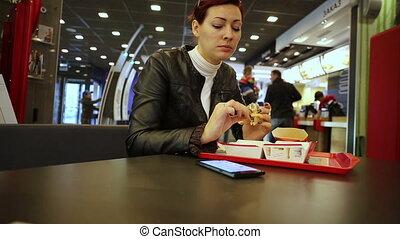regarder, hamburger, smartphone, femme mange
