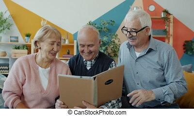 regarder, lent, heureux, gens âgés, film, conversation, rire, album