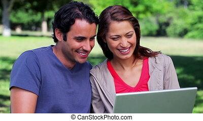 regarder, leur, couple, ordinateur portable, heureux
