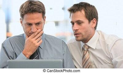 regarder, leur, ordinateur portable, hommes affaires