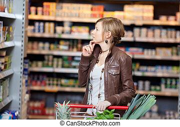 regarder, pensif, femme, produits, supermarché