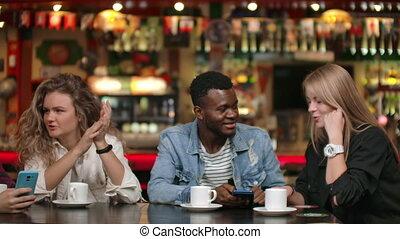 regarder, téléphone, conversation, amis, divers, vidéo, rire, usage, heureux, apps, ensemble, rigolote, table., compagnons, gadget, avoir, réunion, regarder, smartphone, asseoir, multiculturel, amusement, jeune, mobile, ligne