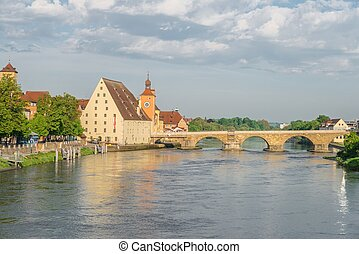 Regensburg in the morning light on a summer day with the promenade and the stone bridge