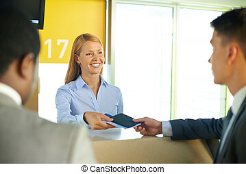 Smiling female returning passport and tickets to businessman in airport