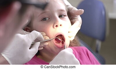 Cropped dentist examining mouth of his little patient