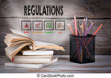 Regulations. Stack of books and pencils on the wooden table.