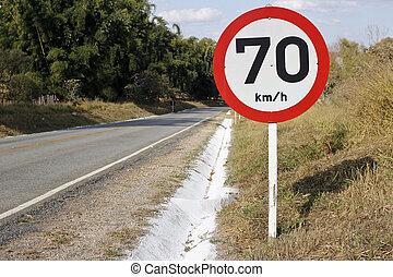 Regulatory board speed of seventy kilometers per hour on paved rural road.