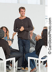 Rehab group applauding happy man standing up at therapy...